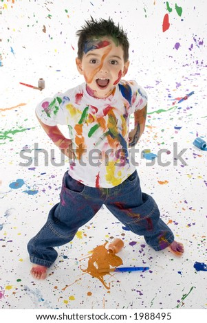 Adorable 3 year old boy child covered in bright paint.  Mess of paint on wall, floor, and child.