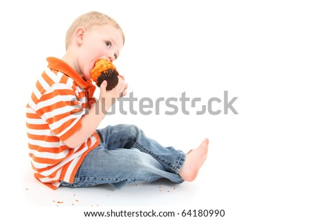 Adorable 2 year old boy eating orange icing cupcake over white background.