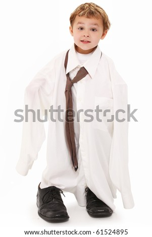 Adorable 4 year old caucasian boy in over sized shirt and tie over white.