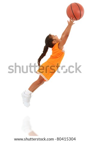Adorable 5 year old girl child in orange sport team uniform jumping for basketball over white background.