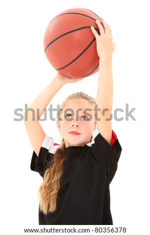Adorable 5 year old girl child making free throw with basketball in uniform over white background.