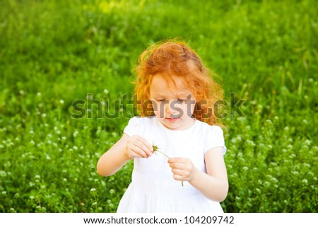 Adorable 3 year old girl playing game with flower, shallow depth of field, focus on foreground