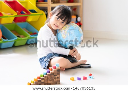 Adorable 4 years old asian little girl is hugging the bilingual globe model contain english and thai language, concept of save the world and learn through play activity for kid education at home.