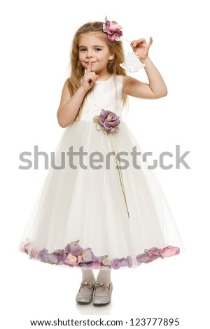 Adorable 6 years old girl in princess dress holding bells with finger on lips, over white background