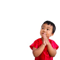 Adorable 2 years old happy cute little Asian boy wear red shirt pose Thai style greeting (wai) with smiling face isolated on white background.