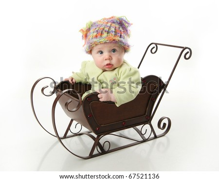 Adorable young baby girl wearing a knit stocking cap sitting in a metal Christmas snow sleigh