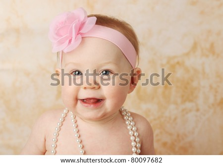 Adorable young baby girl wearing a vintage pearl necklace for When can babies wear jewelry