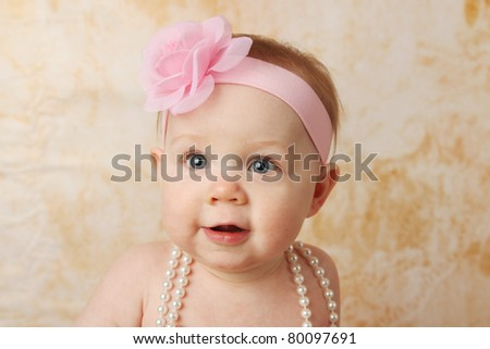 Adorable young baby girl wearing a vintage pearl necklace and pink rose headband