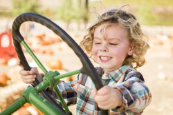 Adorable Young Boy Playing on an Old Tractor in a Rustic Outdoor Fall Setting.