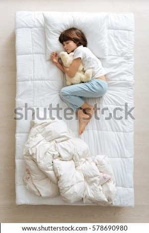 Stock Photo Adorable young boy resting with his toy
