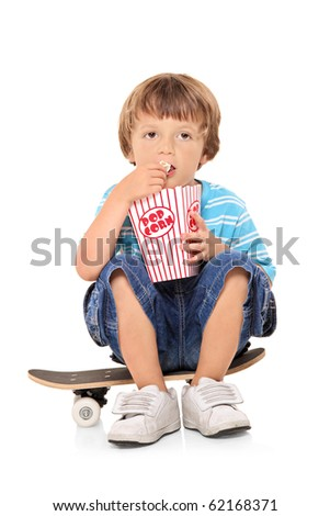 Adorable young boy sitting on a skateboard and eating popcorn isolated against white background