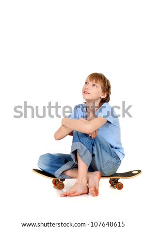 Adorable young boy sitting on a skateboard isolated against white background