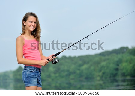 Adorable young brunette girl in pink tank top and denim shorts fishing.