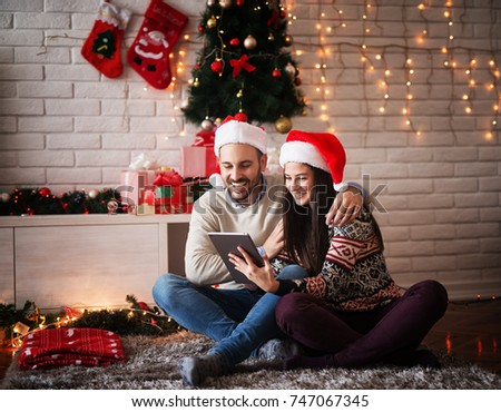 Adorable young couple sitting on a carpet with Santa hats hugged while looking on a tablet for Chrismas holidays.