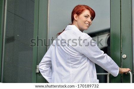 Adorable young female medical professional in white lab coat looks back as she opens the door to her practice or hospital