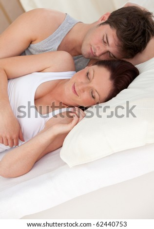 adorable young future parents sleeping on the bed during the morning at home
