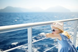 Adorable young girl enjoying ferry ride staring at the deep blue sea. Child having fun on summer family vacation in Greece. Kid sailing on a boat.