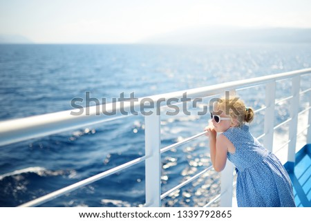 Adorable young girl enjoying ferry ride staring at the deep blue sea. Child having fun on summer family vacation in Greece. Kid sailing on a boat. #1339792865