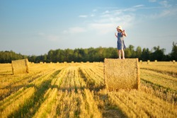 Adorable young girl having fun in a wheat field on a summer day. Child playing at hay bale field during harvest time. Kid enjoying warm sunset outdoors. Harvesting crops in Lithuania.