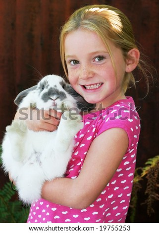 adorable young girl holding pet bunny