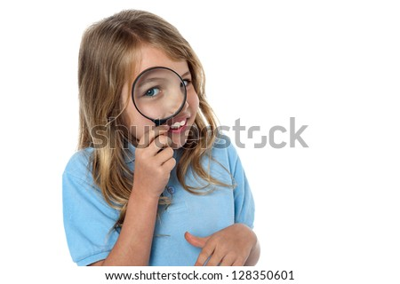 Adorable young girl looking through a magnifying glass, white background.