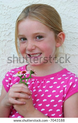 adorable young girl smiling and holding flowers
