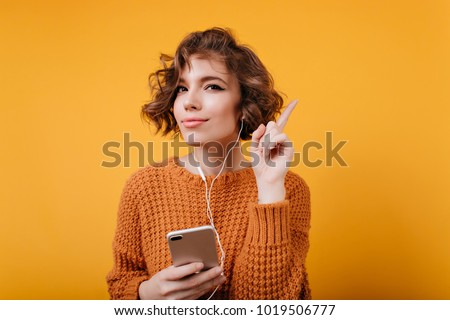 Adorable young lady in cozy attire using smartphone for listening music. Studio shot of magnificent brunette girl in earphones isolated on orange background.