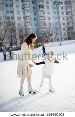 Adorable young mother with her daughter in white clothes on the ice rink