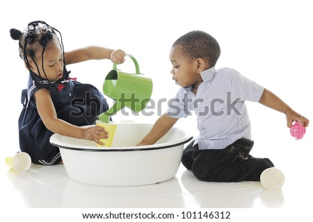 Adorable, young siblings busy in a tub of water and water toys.  On a white background.