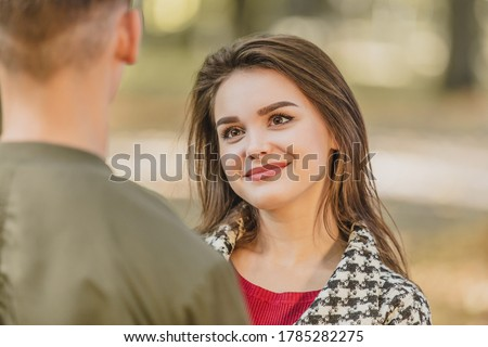 Adorable young woman is looking at her boyfriend, standing back to the camera, with big admiration and appreciation. Stock photo ©