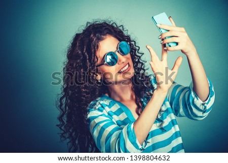 Adorable young woman, young girl with brunette curly hair taking a selfie, smiling to camera of her cell phone. Wearing round sunglasses, in white blue striped shirt. Isolated on blue wall background.