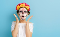 Adorable zombie in flower wreath posing on blue background. Happy child with Halloween creative makeup. Girl celebrating for Mexican Day of the Dead.