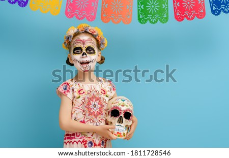 Photo of  Adorable zombie in flower wreath posing on blue background. Happy child with Halloween creative makeup. Girl celebrating for Mexican Day of the Dead.