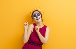 Adorable zombie in flower wreath posing on yellow background. Happy woman with Halloween creative makeup. Girl celebrating for Mexican Day of the Dead.
