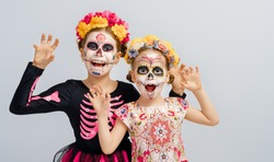 Adorable zombies in flower wreaths posing on white background. Happy children with Halloween creative makeup. Girls celebrating for Mexican Day of the Dead.