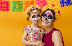 Adorable zombies in flower wreaths posing on yellow background. Happy family with Halloween creative makeup. Girls celebrating for Mexican Day of the Dead.