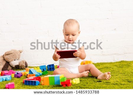 adorbale kid sitting among toys on green floor and holding digital device #1485933788