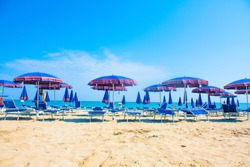 Adriatic Sea coast view. Seashore of Italy, summer umbrellas on sandy beach with clouds on horizon