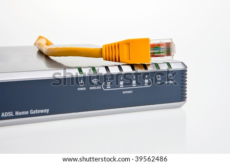 ADSL internet modem/router, front panel displays with yellow patch cord. - stock photo