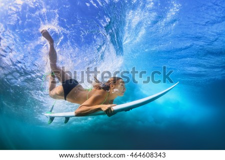 Adult active girl in bikini in action - surfer with surf board dive underwater under breaking big ocean wave. Family lifestyle, people water sport adventure camp, beach extreme swim on summer vacation