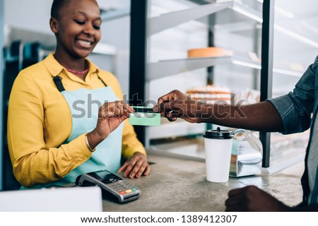 Adult African American barista smiling and taking credit card from crop black man while standing behind counter and selling food in modern cafe