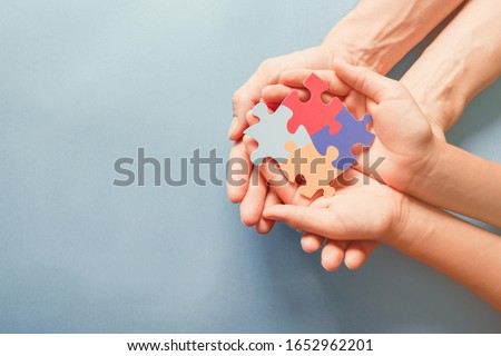 Adult and chiild hands holding jigsaw puzzle shape, Autism awareness, Autism spectrum disorder family support concept, World Autism Awareness Day