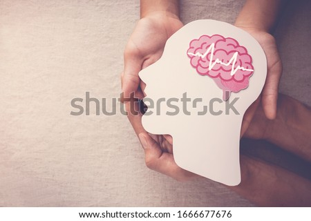 Adult and child hands holding encephalography brain paper cutout,autism, Epilepsy and alzheimer awareness, seizure disorder, stroke, ADHD, world mental health day concept