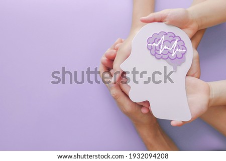Adult and child hands holding encephalography brain paper cutout,autism, Stroke, Epilepsy and alzheimer awareness, seizure disorder, stroke, ADHD, world mental health day concept Foto stock ©