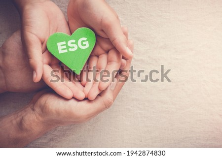 Adult and child hands holding green heart with ESG, Environmental, social and corporate governance concept Foto stock ©