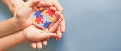 Adult and child hands holding jigsaw puzzle heart shape, Autism disorder awareness, Autism spectrum family support concept, World Autism Awareness Day