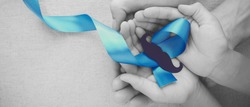 Adult and child hands holding Light blue ribbons with mustache , Prostate Cancer Awareness, Men health awareness, Movember month