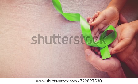 Adult and child hands holding Lime Green Ribbon, panoramic banner background, Mental health awareness and Lymphoma Awareness #722897530