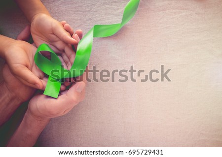 Adult and child hands holding Lime GreenRibbon, toning background, Mental health awareness and Lymphoma Awareness