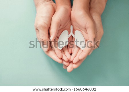 Adult and child hands holding lung, world tuberculosis day, world no tobacco day, coronavirus covid-19,  Pneumonia,Pulmonary hypertension, copd, eco air pollution,organ donation, healing concept Stock photo ©